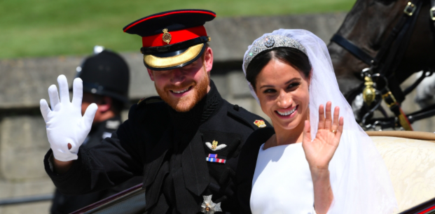 Meghan Markle and Prince Harry smile and wave to the large crowd that gathered outside the chapel as they embark in a horse-drawn carriage to their wedding reception.