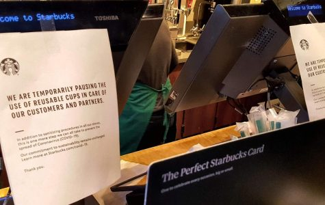 Posters taped to a register at a Starbucks in Charlottesville, Virginia letting customers know that reusable cups will not be used during the ongoing COVID-19 outbreak.