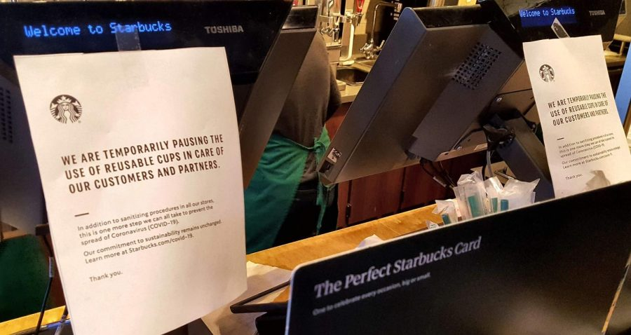Posters+taped+to+a+register+at+a+Starbucks+in+Charlottesville%2C+Virginia+letting+customers+know+that+reusable+cups+will+not+be+used+during+the+ongoing+COVID-19+outbreak.+